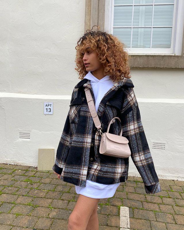 Garota usando casaco xadrez por cima de blusa de moletom oversized branca e uma bolsa atravessada bege. Ela está olhando para o lado e a foto só pega até a a altura da coxa.