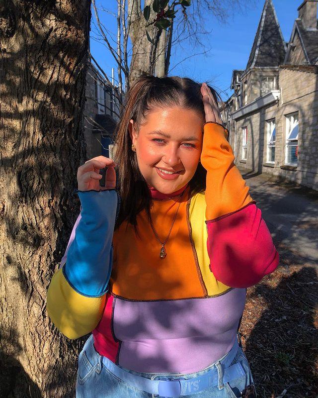 Garota usando blusa de patchwork azul, amarela, laranja, rosa e lilás. Ela está sorrindo, com uma das mãos no cabelo, e a outra levantada perto do rosto.