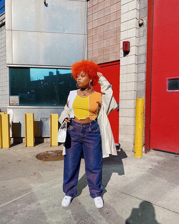 Garota usando blusa cropped branca, laranja e amarela de patchwork com calça jeans baggy, tênis branco e casaco bege. Ela está em pé, com uma das mãos no cabelo crespo vermelho e, a outra, segurando uma bolsa branca pequena. Sua expressão facial é séria e ela está olhando para o lado.