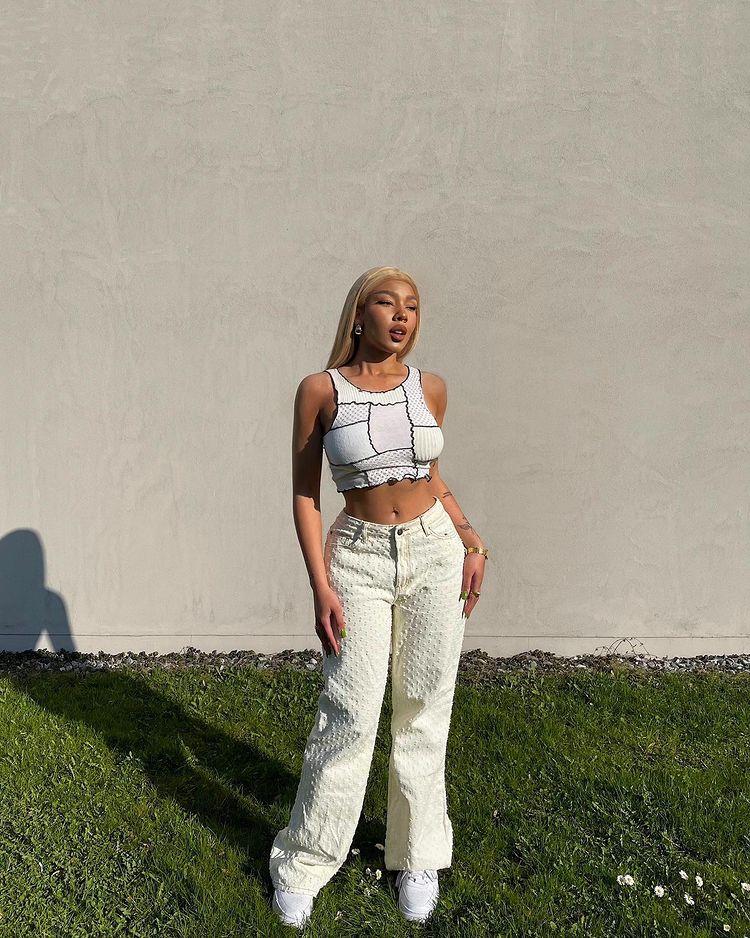 Garota usando blusa cropped branca de patchwork com calça baggy amarela-clara e tênis branco. Ela está em pé, com as duas mãos apoiadas na perna, expressão séria olhando para o lado.