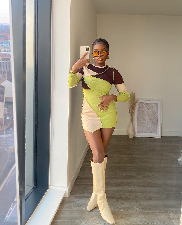 Garota usando vestido de patchwork de manga longa nas cores verde neon, bege e marrom. Ela está com uma bota bege clara de bico quadrado que vai até o joelho e óculos com lentes alaranjadas. Ela está em pé, tirando a foto com o celular em uma das mãos, enquanto a outra está na cintura.