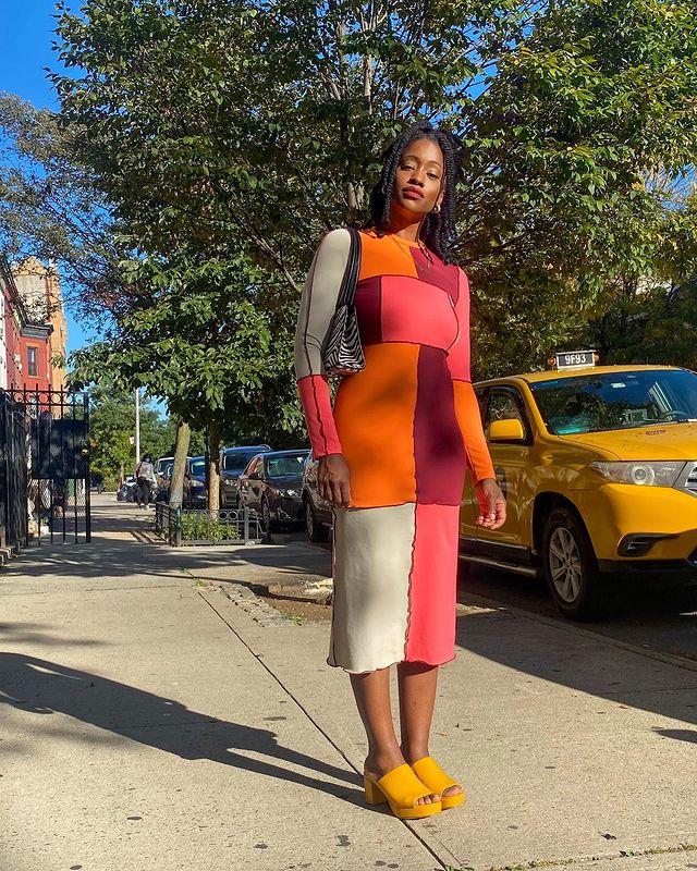 Garota usando vestido midi de manga longa de patchwork nas cores laranja, bordô, vermelho e bege. Ela está com um tamanco amarelo e uma bolsa de estampa de zebrinha pendurada em um dos ombros. Ela está em pé, olhando em direção à câmera, que tira a foto de cima para baixo.