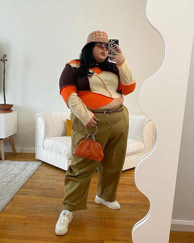 Garota usando blusa de manga longa de patchwork nas cores laranja, bege e marrom. Ela está usando uma calça baggy bege escura, com cinto fino marrom, tênis branco e um bucket hat xadrez laranja e marrom. Ela está em pé, tirando foto em frente a um espelho com o celular na mão, e uma bolsa pequena laranja na outra, além de óculos de sol com lentes marrons.