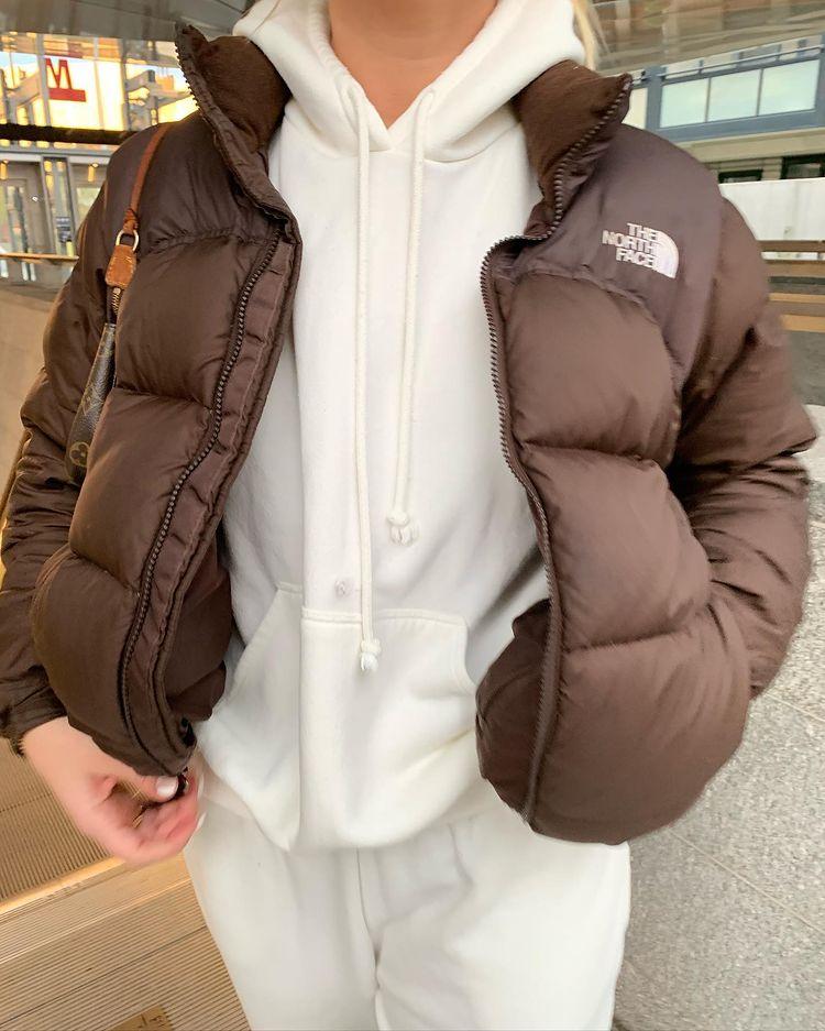 Mulher usando conjunto de moletom off-white com jaqueta puffer marrom por cima. A foto só dá para ver do pescoço pra baixo e pega um pouco da calça. Uma das mãos está no bolso.