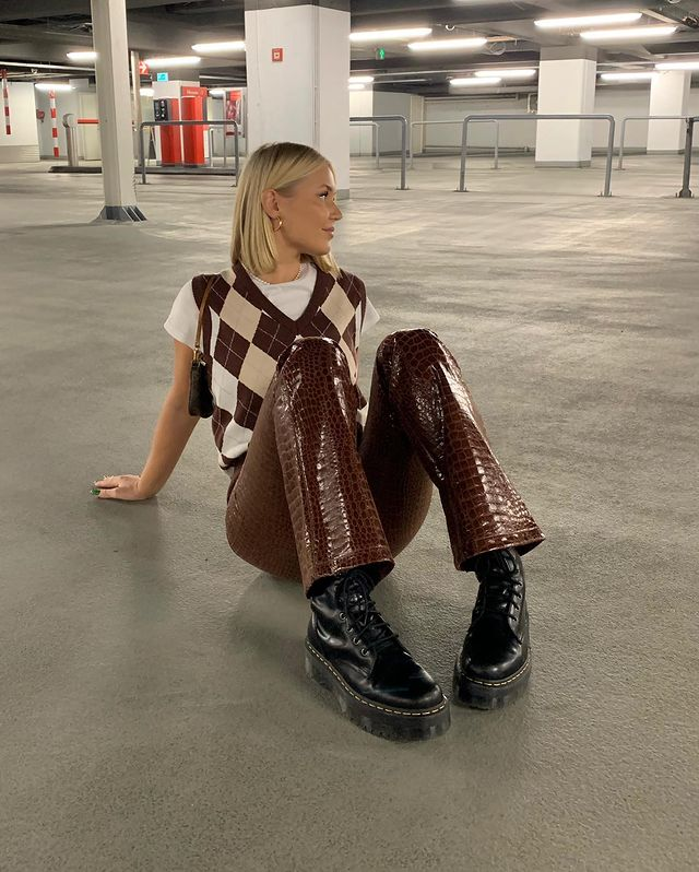 Garota sentada no chão com os joelhos dobrados para frente e as duas mãos no chão, para trás das costas. Ela usa um colete xadrez por cima de uma camiseta branca, uma calça marrom de vinil com textura croco e um coturno preto.