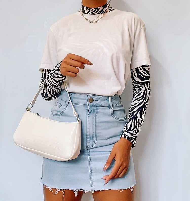 Garota usa blusa segunda pele por baixo de camiseta bege básica, com saia jeans clara e bolsa baguete off-white pendurada em um dos braços. A foto mostra apenas do pescoço para baixo até a altura da coxa.