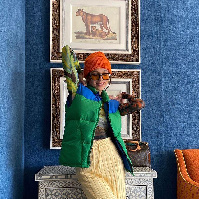 A influenciadora americana Emma Chamberlain usando colete verde e azul por cima de blusa segunda pele preta com tons de verde, calça de tricô amarela, gorro laranja e óculos de sol com lentes alaranjadas. Na foto, do joelho para cima, ela está com os dois braços dobrados para trás.