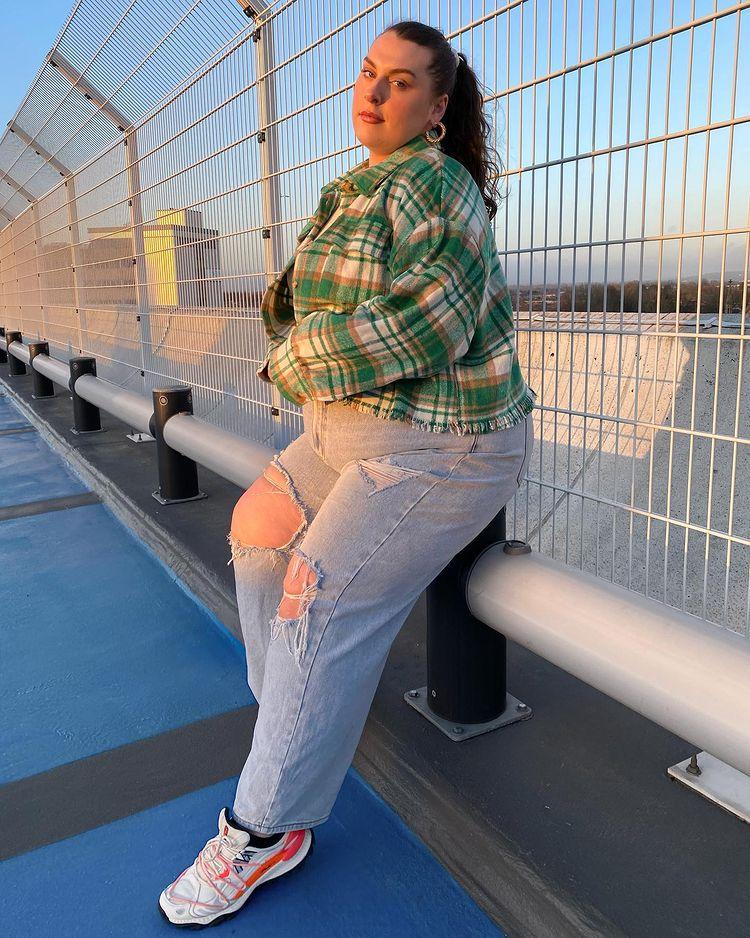 Garota está usando casaco verde xadrez com calça jeans rasgada e tênis branco e laranja. Ela está apoiada em corrimão.