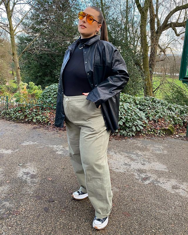 Mulher usando blusa preta de manga longa com calça larga verde, casaco preto de couro alongado, tênis All Star preto e branco de cano baixo e óculos de sol de lentes alaranjadas. Ela está em pé, com a cabeça e o corpo levemente inclinados.