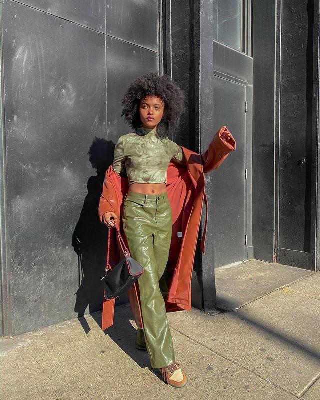 Garota está usando top cropped verde, calça verde oliva de couro, casaco longo laranja de couro e uma bolsa pendurada na mão. Uma perna está na frente da outra, e um braço está levemente levantado.