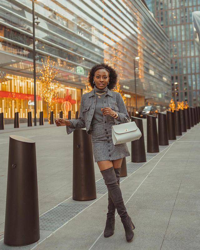 Garota está usando um look todo cinza com blusa de gola alta, casaco curto, saia de botões na frente e bota over the knee. Ela carrega uma bolsa pequena em um dos braços, e uma das pernas está cruzada na frente da outra.