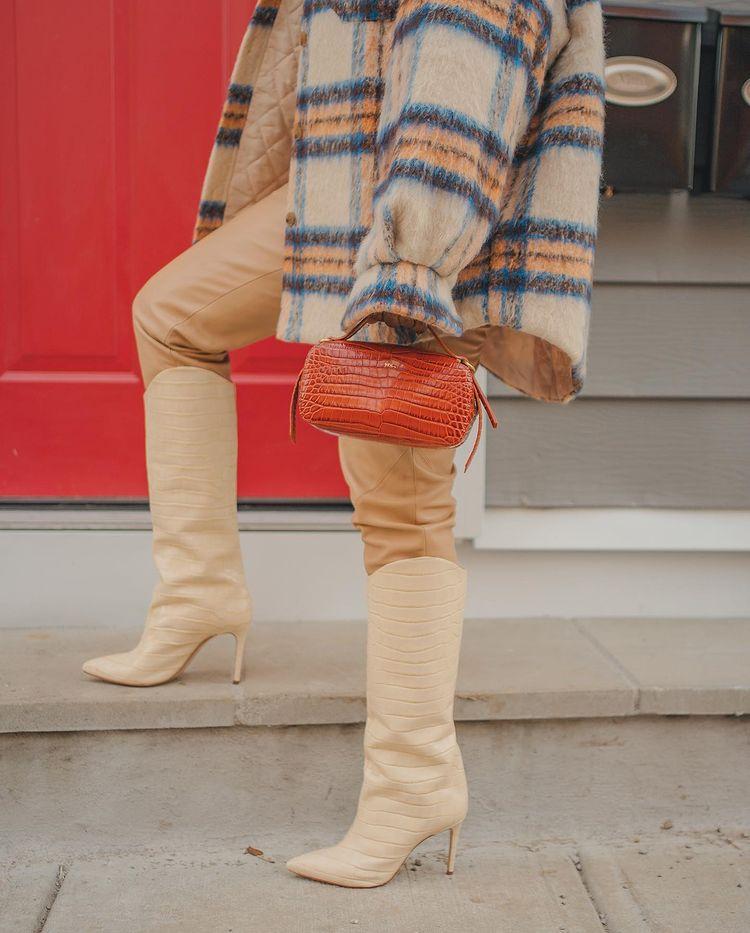 Na foto, aparece parte de uma camisa xadrez de flanela, calça bege e bota estilo cowboy com salto fino e textura croco também bege, além de uma bolsa laranja com textura croco segurada por uma das mãos da garota.