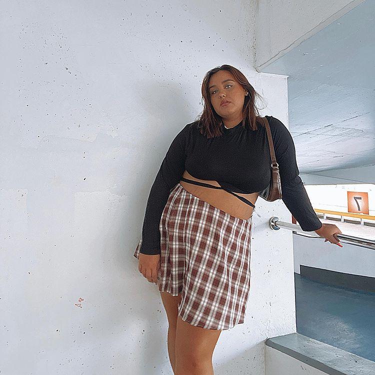 Garota está usando blusa de manga longa cropped preta com saia xadrez marrom e off-white e uma bolsa baguete pendurada em um dos ombros. Ela está com o corpo inclinado e uma das mãos apoiadas em um corrimão.