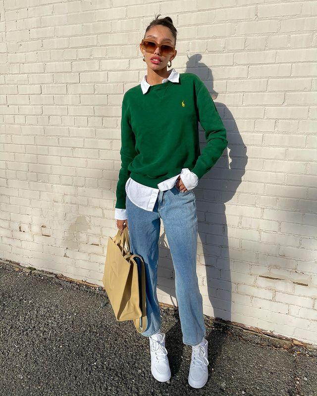 Garota usando camisa branca por baixo de suéter verde bandeira, calça jeans larguinha, tênis branco e uma das mãos segurando uma bolsa grande amarela-clara. Ela está em pé com uma das mãos no bolso.