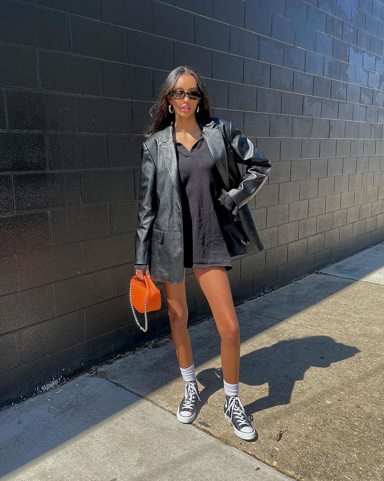 Mulher usando vestido preto com casaco preto de couro alongado, óculos de sol retangulares pretos. Ela está segurando uma minibolsa laranja com uma das mãos, usando All Star preto e meias brancas nos pés. Uma das mãos está na cintura e uma das pernas está levemente flexionada.