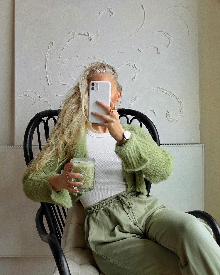 Garota está usando camiseta branca com casaco e calça de moletom verdes. Ela está sentada em frente a um espelho e tira a foto com o celular na frente do seu rosto.