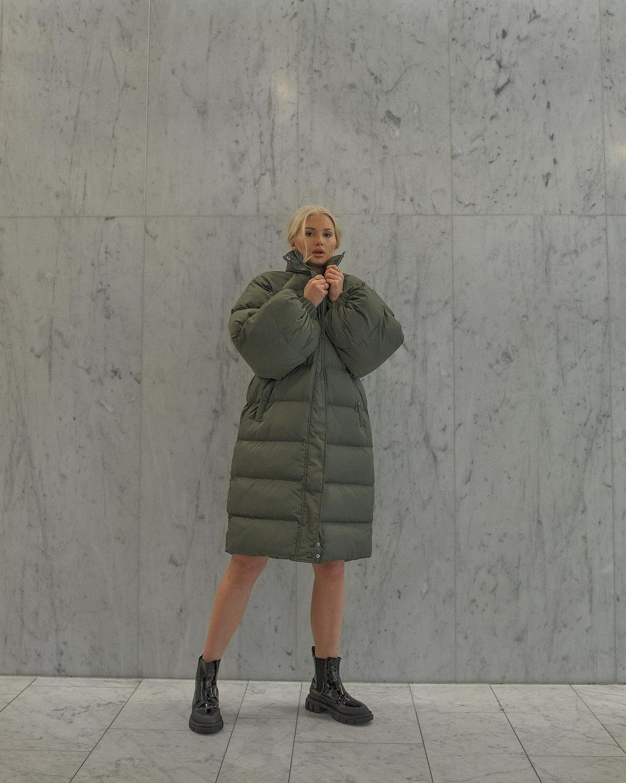 Mulher usando jaqueta puffer verde que vai até o joelho com bota de cano curto preta tratorada. Ela está com os braços dobrados em direção ao queixo.