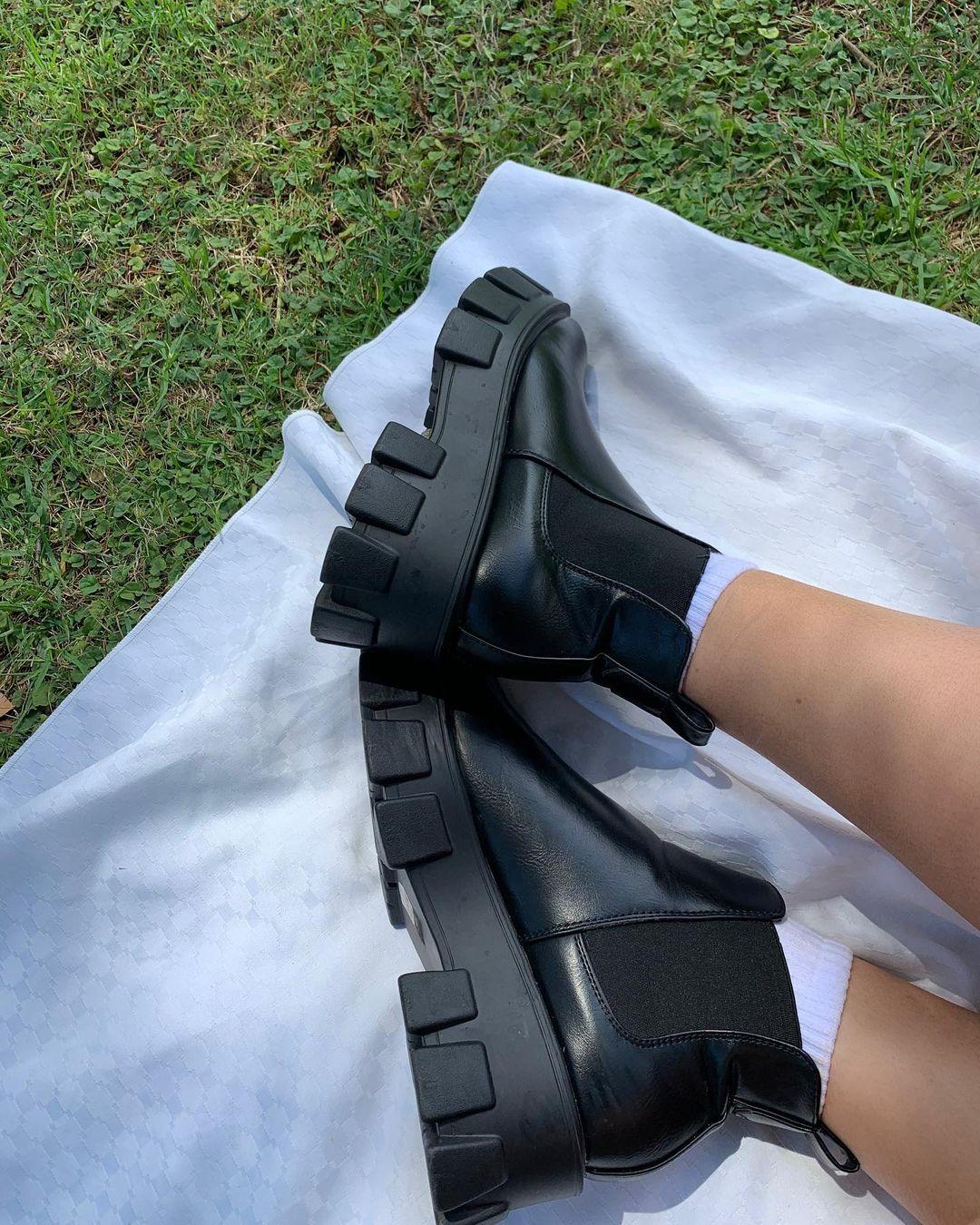Bota preta tratorada de cano curto. Na foto, só dá para ver os pés e parte da canela. Os pés estão apoiados em um tecido branco, que está em cima da grama.