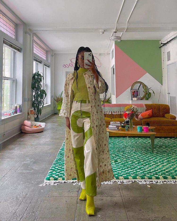 Mulher está usando blusinha verde de gola alta, calça branca com detalhes em verde, bota de bico quadrado verde e casaco longo com estampa floral delicada. Ela está em frente a um espelho, de pé, tirando a foto com o celular cobrindo o rosto.