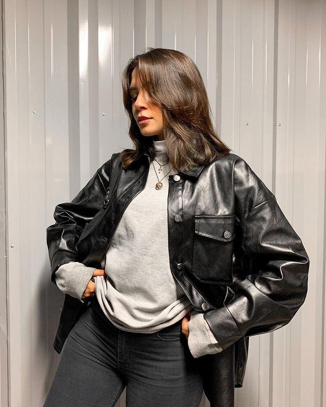 Garota usando moletom cinza por baixo de casaco preto de couro. Ela está com o rosto virado para o lado e as duas mãos na cintura.