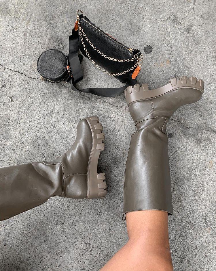 Mulher usa uma bota cinza tratorada que vai até a altura do joelho. Na foto, só dá para ver a bota e uma parte das pernas. Ao lado, tem uma bolsa preta de nylon.
