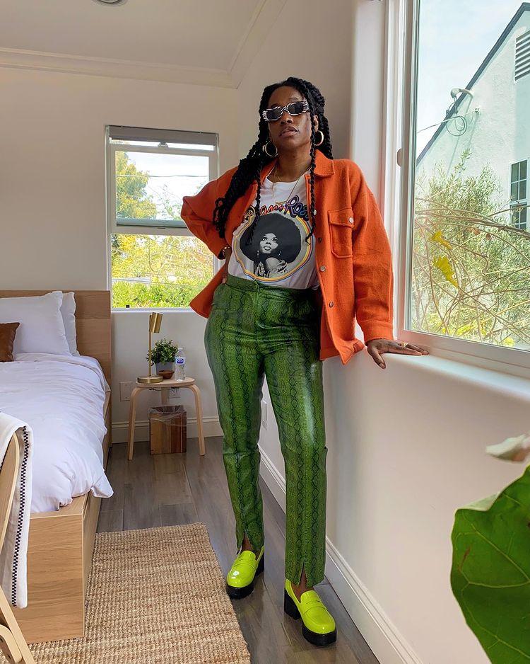 Mulher usando camiseta branca com casaco laranja, calça verde de estampa de cobra e oxford verde neon. Ela está com uma das mãos na cintura e a outra apoiada em uma janela.