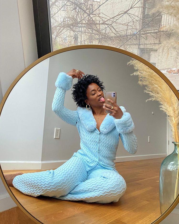 Mulher está usando conjunto confortável azul claro com casaquinho que tem pelos nos punhos e na gola e calça. Ela está em frente ao espelho, sentada com as pernas dobradas e com o celular próximo ao rosto.