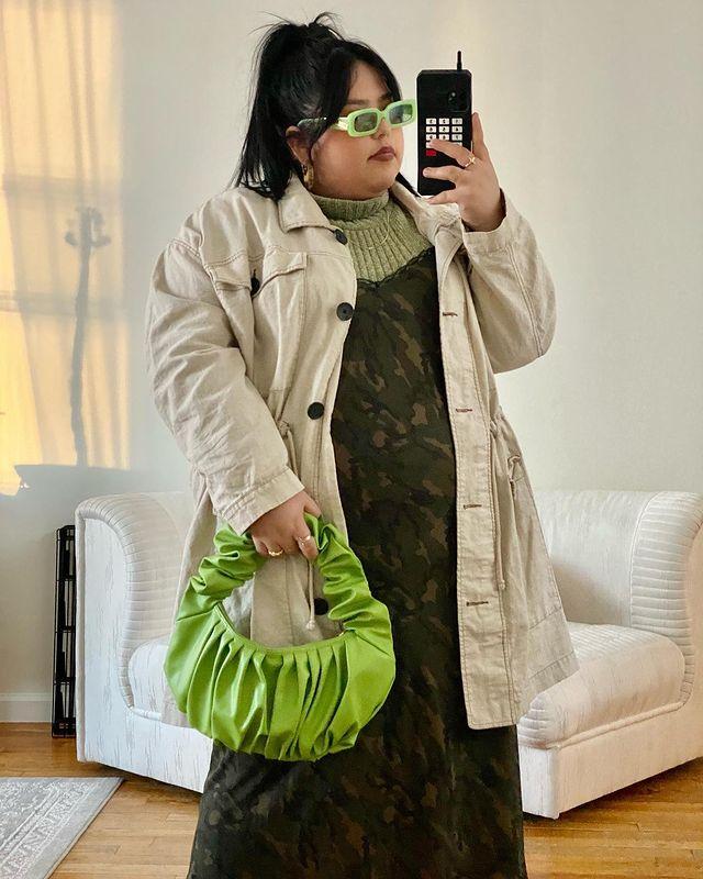 Mulher está usando uma blusa de gola alta verde com vestido verde escuro por cima, casaco bege de botões, bolsa e óculos de sol em verde neon. Ela está em frente ao espelho tirando a foto com o celular na mão.