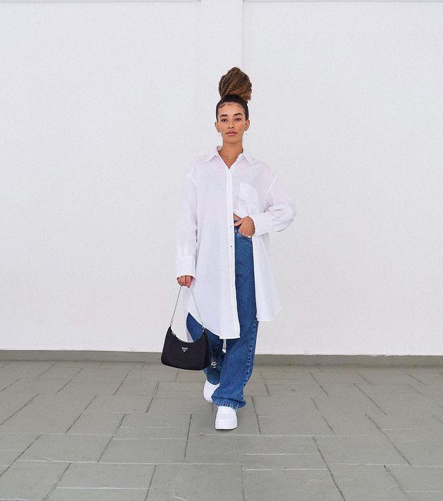 Mulher está usando camisa branca oversized com calça jeans baggy, tênis branco e bolsa preta em uma das mãos. Ela está em pé, os cabelos presos em um coque e uma das mãos na cintura.