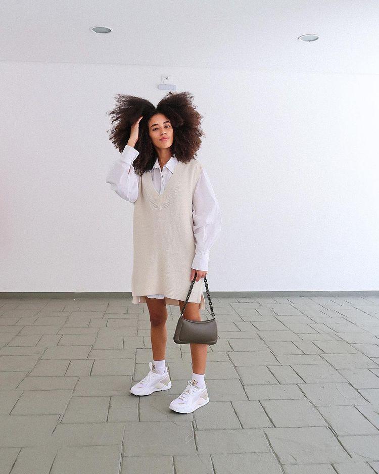 Garota usando camisa branca por baixo de colete bege oversized e tênis branco. Uma das mãos está segurando uma bolsa baguete cinza, e a outra está mexendo no cabelo crespo.