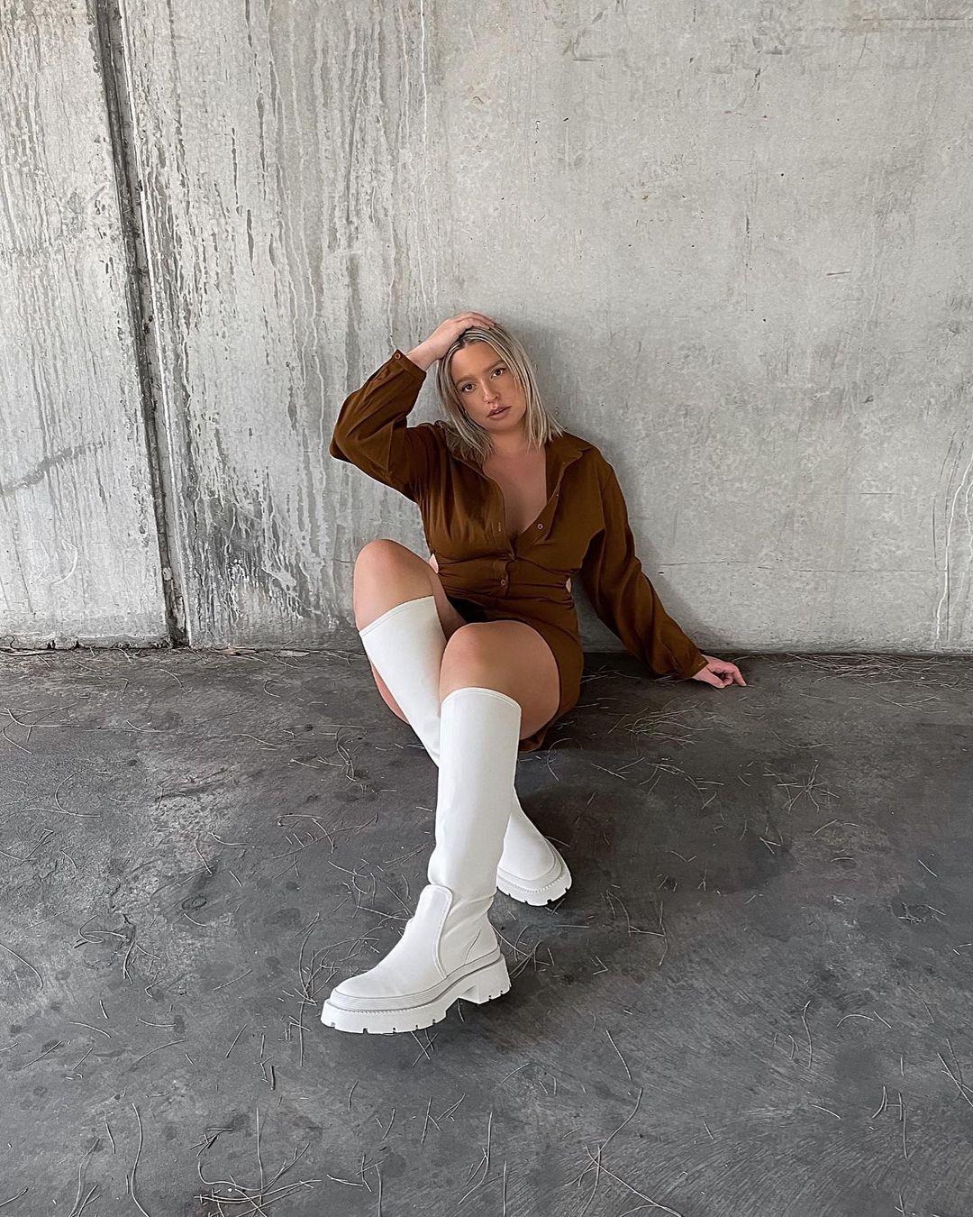 Mulher usando vestido marrom com mangas longas e bota até a altura do joelho off-white com sola tratorada. Ela está sentada no chão com uma mão na cabeça, a outra apoiada atrás e as pernas cruzadas.