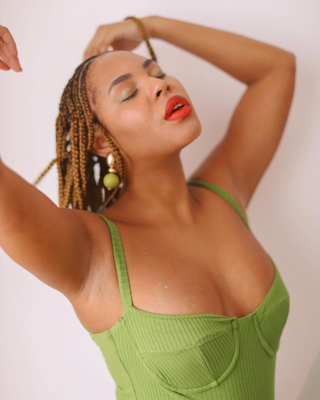 Garota usando body verde com decote meia taça. Ela está numa pose espontânea com a cabeça levemente inclinada para cima, os olhos fechados, batom vermelho, brinco dourado e verde, com os braços para trás da cabeça.