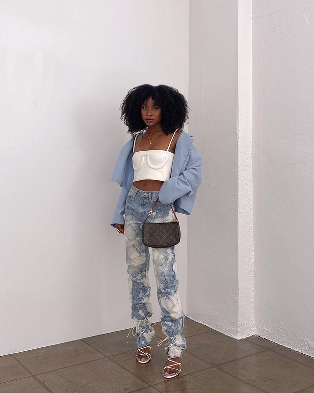 Garota usando top cropped branco com jaqueta azul oversized, calça jeans tie-dye e sandália branca com amarrações por cima da calça. Ela está segurando uma bolsa da Louis Vuitton com uma das mãos e sua expressão facial é séria.