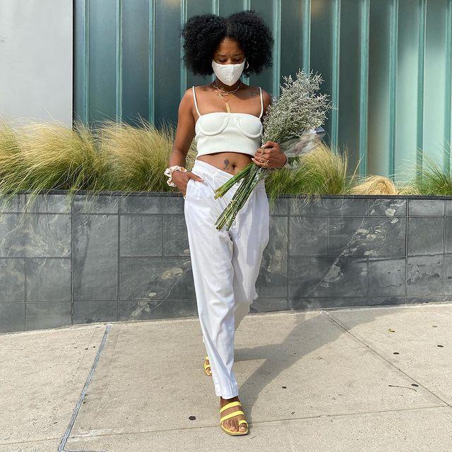 Garota usando top cropped off white com calça branca de tecido e rasteirinha amarela. Ela está usando uma máscara de proteção branca, olhando para baixo e segurando um buquê de flores com uma das mãos, enquanto a outra está no bolso.