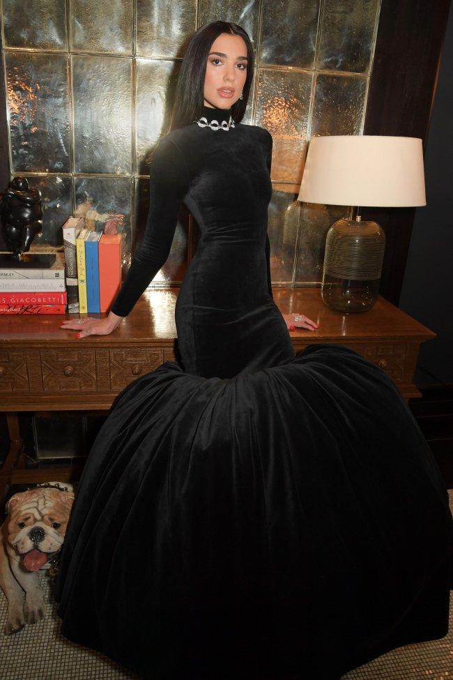 Dua Lipa encostada em uma mesa com livros e um abajur, usando um vestido longo preto de veludo, com os cabelos penteados para trás e com uma expressão séria.