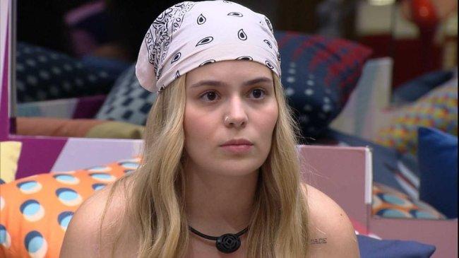 Viih Tube olhando séria para algo ou alguém. Ela está com o cabelo solto e usa um lenço branco com estampas pretas amarrado na cabeça