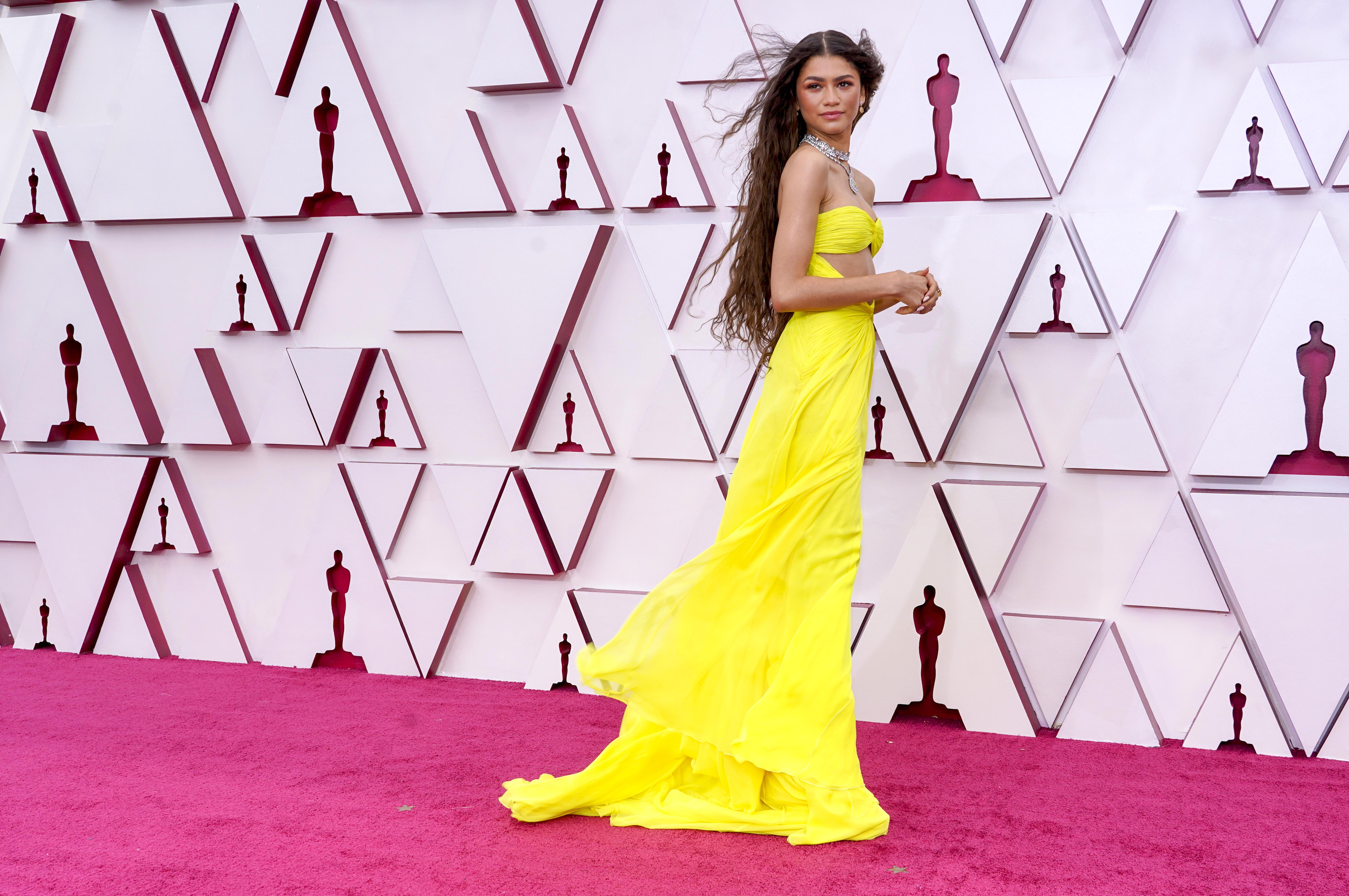 Zendaya usando vestido amarelo esvoaçante no Oscar 2021. Ela está com o corpo de lado, cabelo solto aos ventos, as mãos na frente do corpo e olhando para o lado com expressão facial séria.