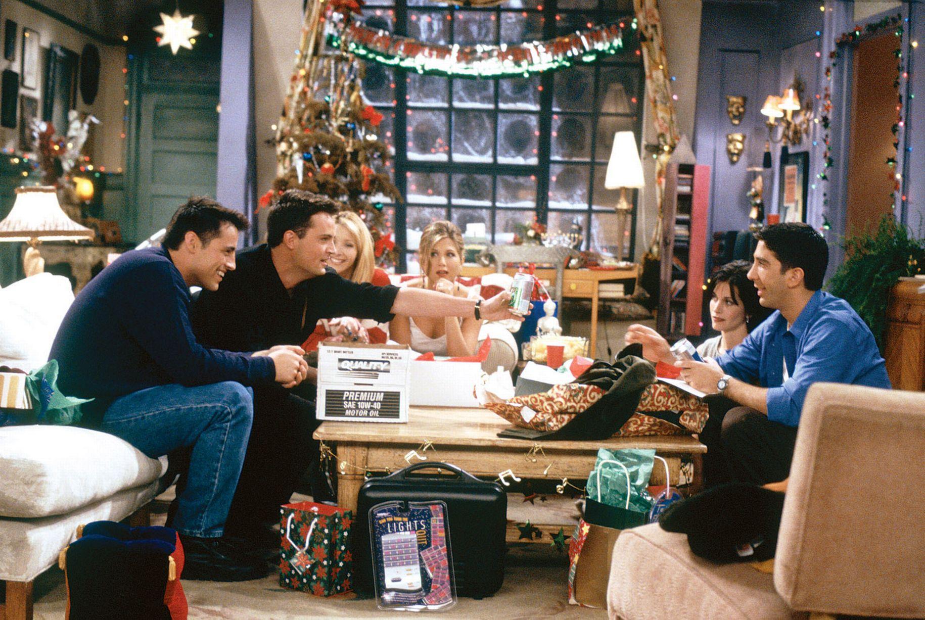 Cena de Friends em que os seis personagens principais estão sentados na sala entregando presentes; eles estão organizados em volta da mesa e ao fundo é possível ver a decoração natalina