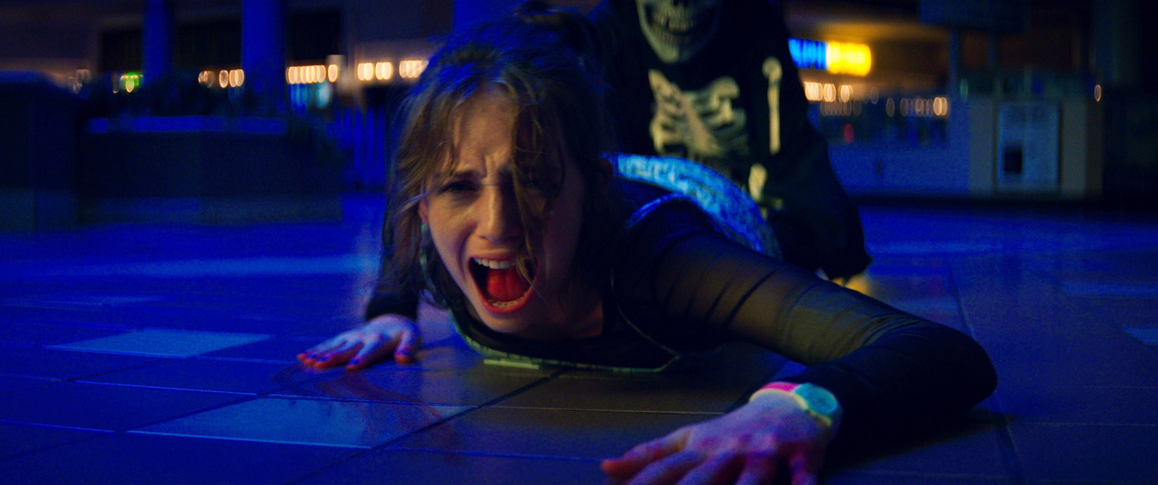 Maya Hawke como Heather em imagem promocional de Rua do Medo, ela está gritando enquanto alguém a arrasta pelo chão