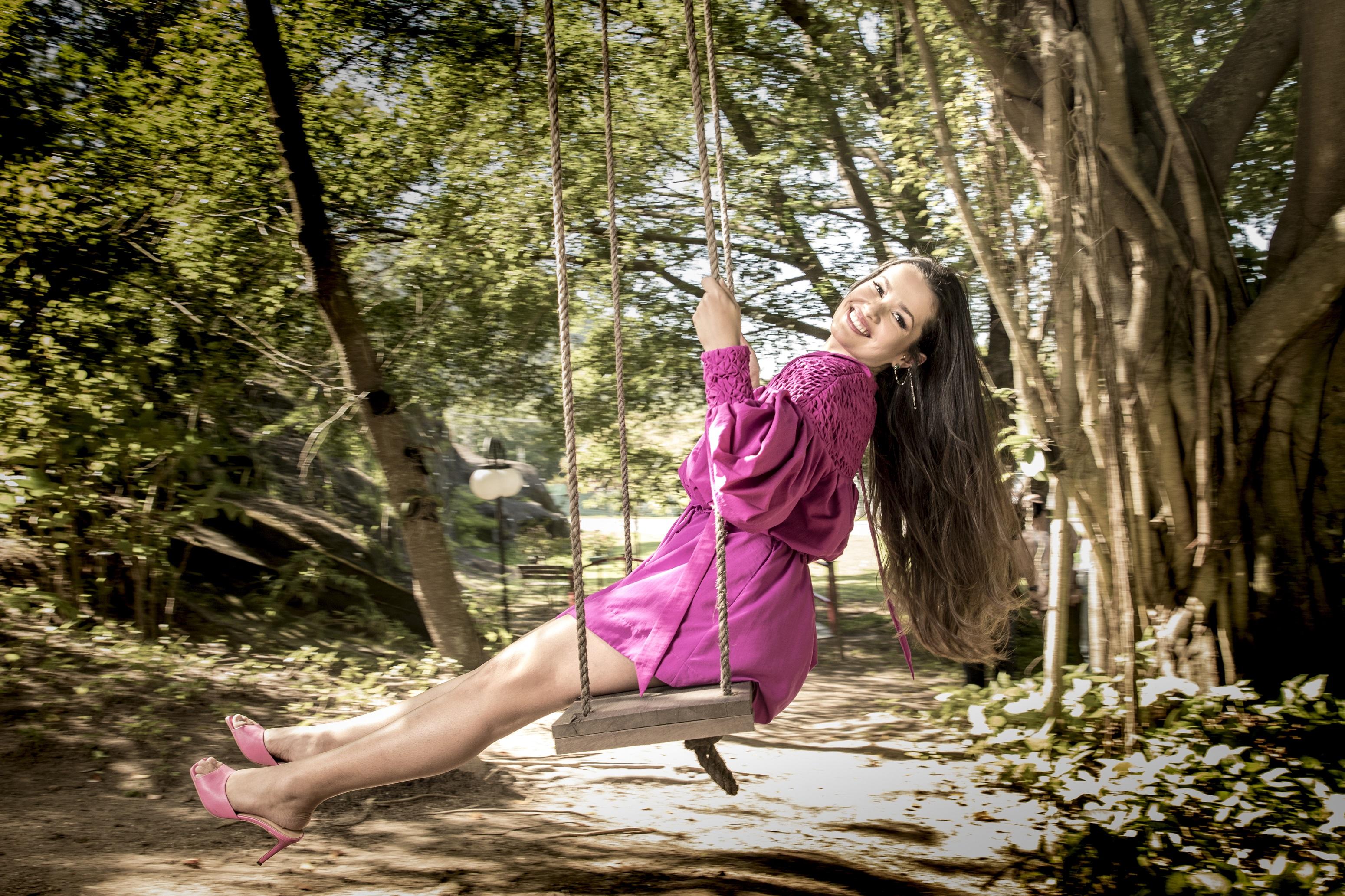 Juliette, vencedora do BBB21, em um balanço no meio de uma floresta usando um vestido rosa, sorrindo para câmera