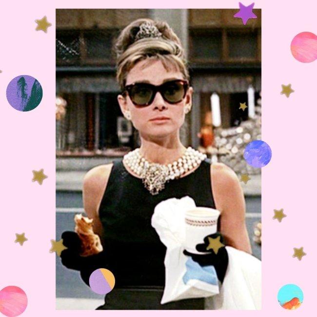 Audrey Hepburn como Holly, no filme Bonequinha de Luxo, segurando um saco branco com um copo de café e croissant, usando o vestido preto com colares, e óculos preto, com expressão séria.
