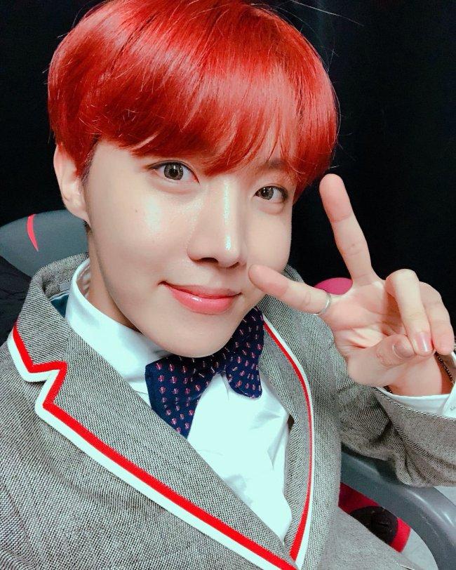J-hope, do grupo BTS, com cabelo colorido, fazendo sinal de paz e amor, usando gravata borboleta e blazer cinza com lista vermelha e branca.