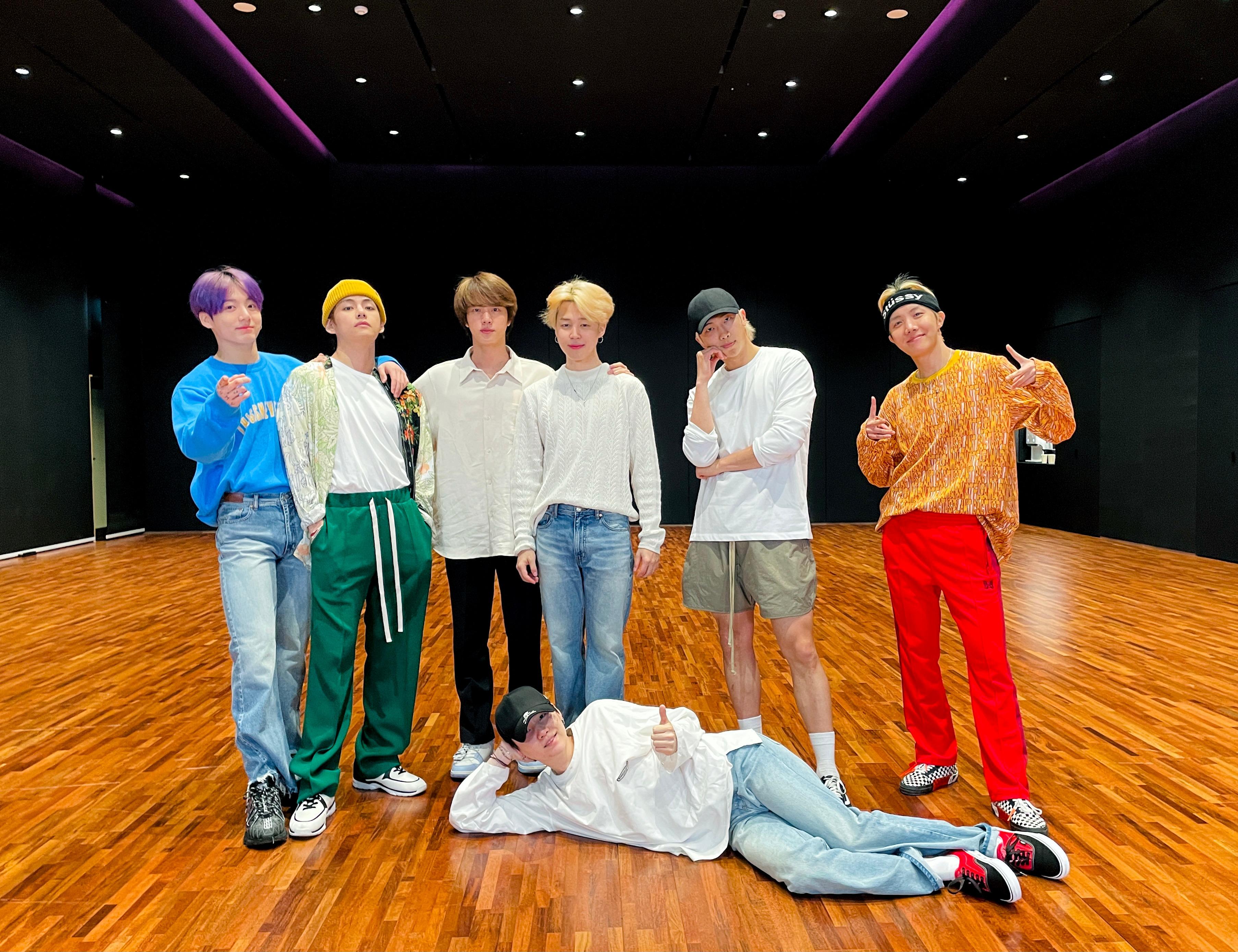 Os sete membros do BTS em foto de divulgação; seis deles estão em pé alinhados na horizontal enquanto um está deitado de lado no chão com a cabeça apoiada o braço; todos estão posando para câmera