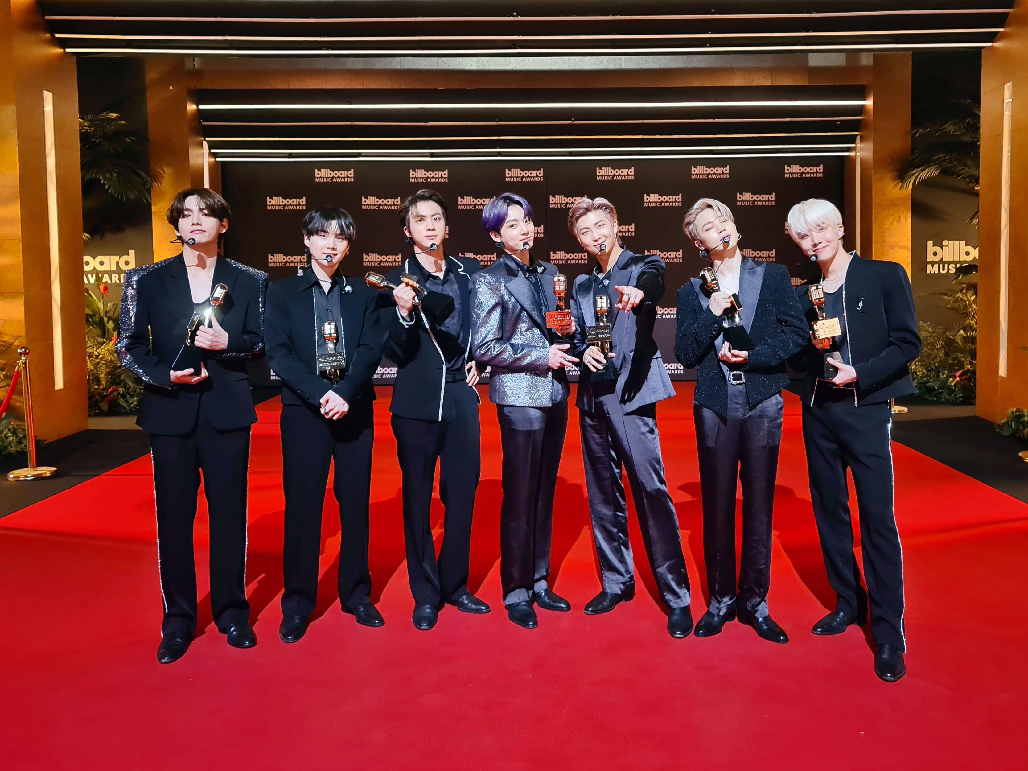 Sete integrantes do grupo BTS no red carpet do Billboard Music Awards 2021; eles estão alinhados na horizontal, cada um segurando um prêmio com roupas sociais escuras