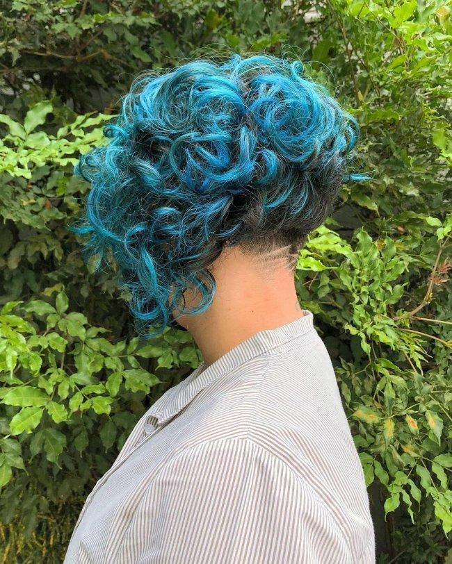 Jovem de costas com cabelo colorido azul, usando camisa branca.