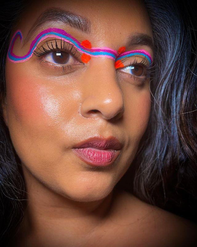 Foto com close no rosto de uma jovem com cabelo escuro, exibindo sua maquiagem com delineado unificado com traços rosa, azul e vermelho. Sua expressão é séria.