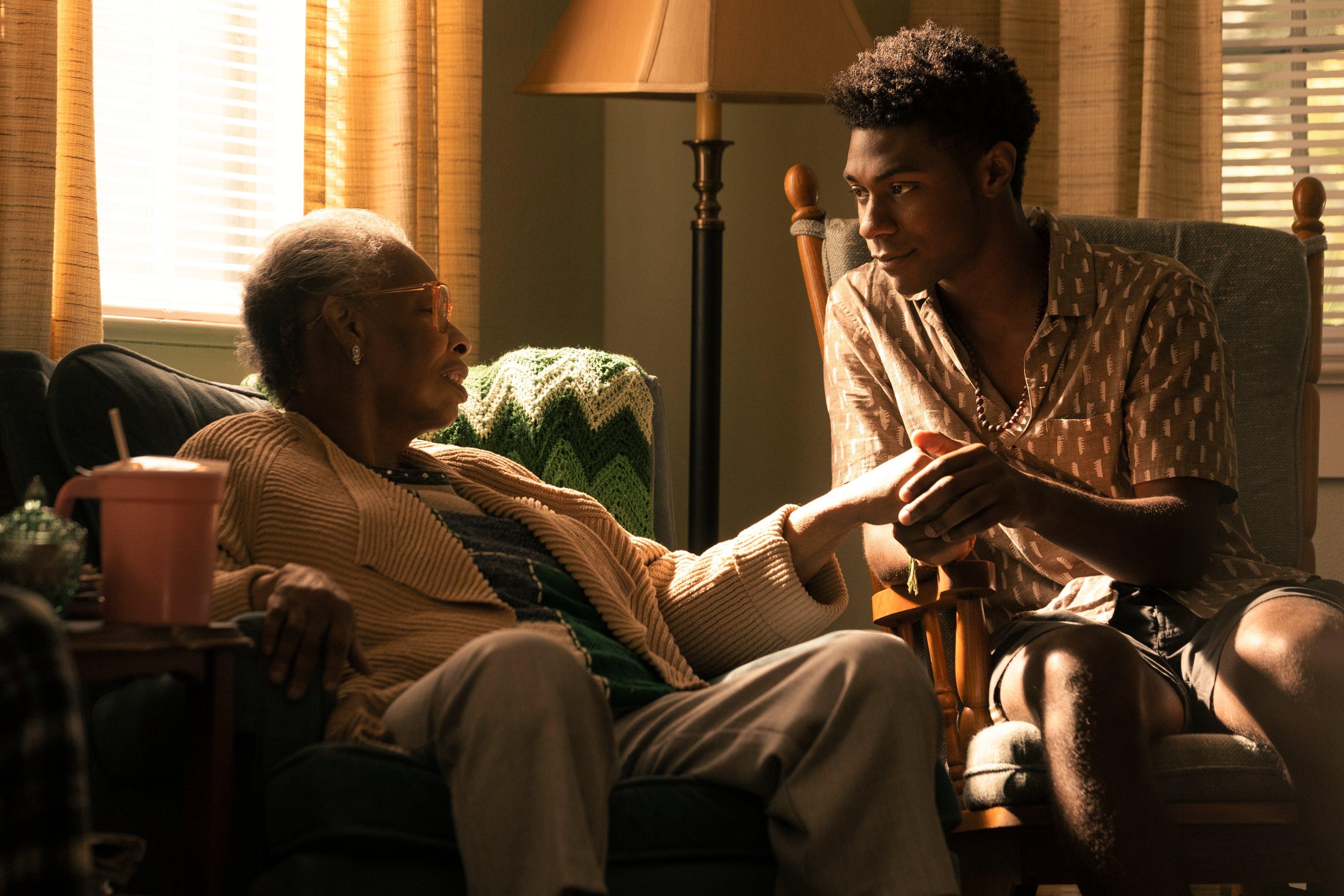 Pope e senhora que parece ser sua avó, eles estão segurando a mão um do outro sentados em uma sala em cena de Outer Banks