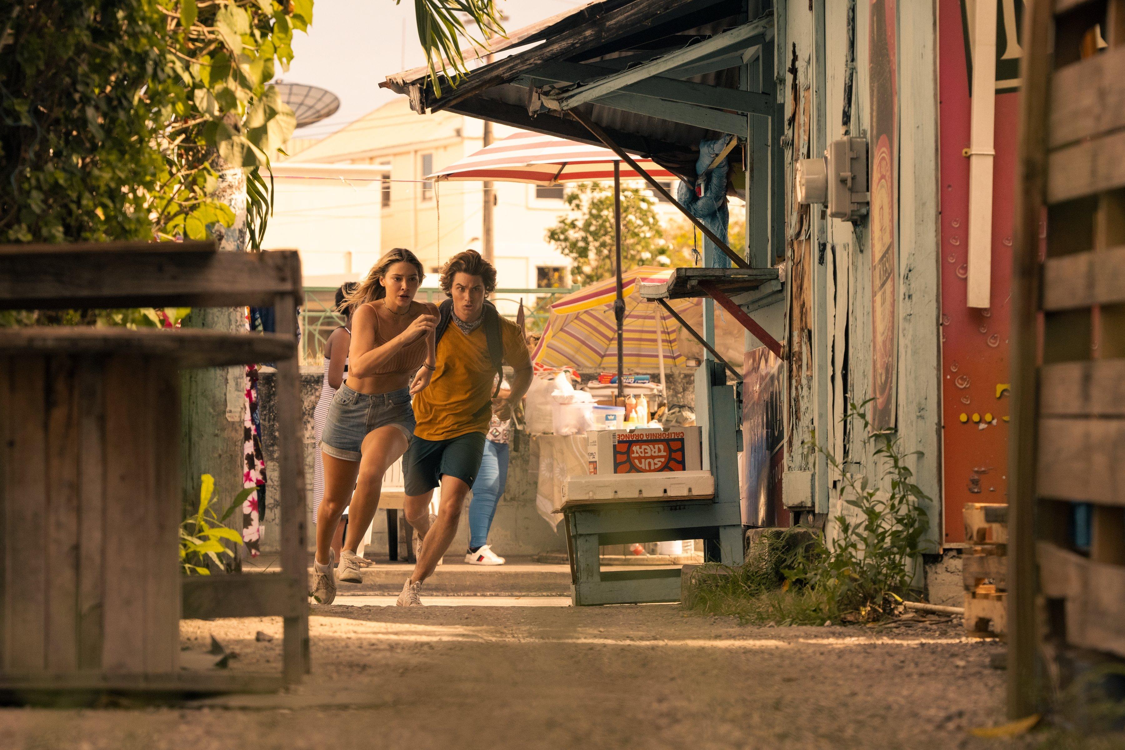 Sarah e John B. correndo juntos em cena de Outer Banks, eles estão na rua e parecem estar fugindo de alguém