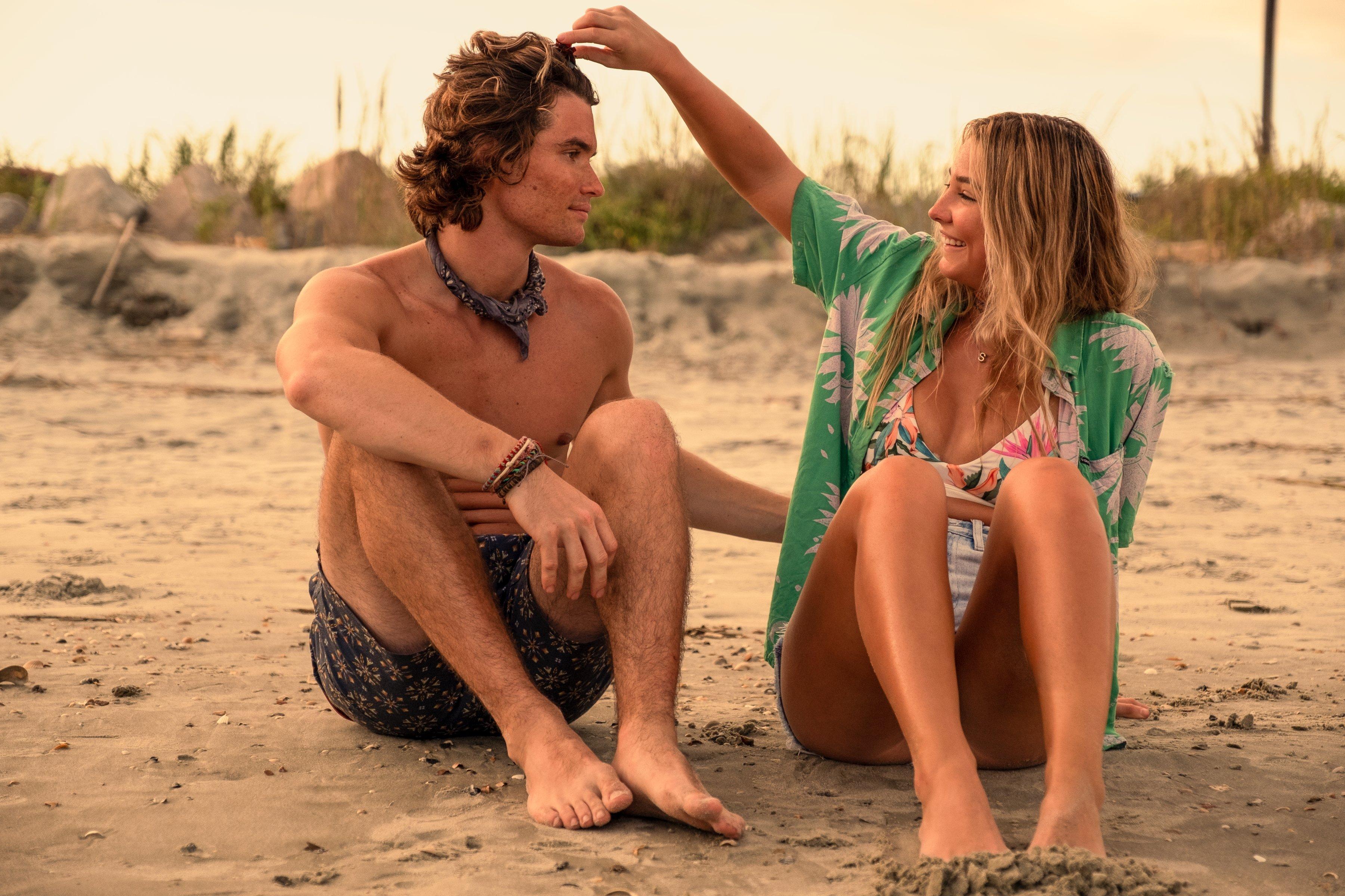 Sarah mexendo no cabelo de John B. em cena de Outer Banks; os dois estão sentados na praia, ele sem camisa e ela de shorts e biquíni com kimono verde