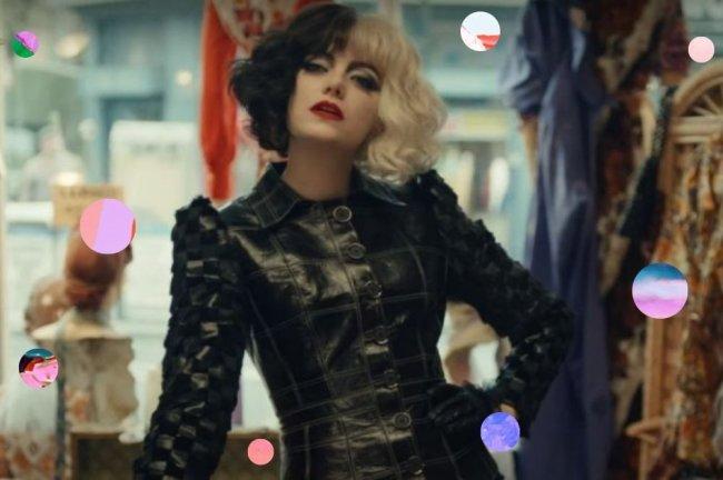 Emma Stone no filme Cruella, vestida como a personagem, usando peruca de cabelo na cor preta e branca, jaqueta de couro preta, com a mão na cintura com expressão séria.